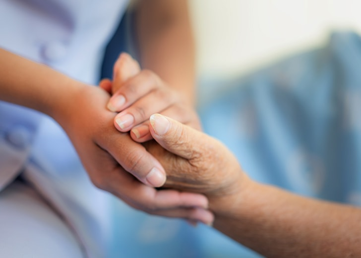 nurse holding elderly woman hands