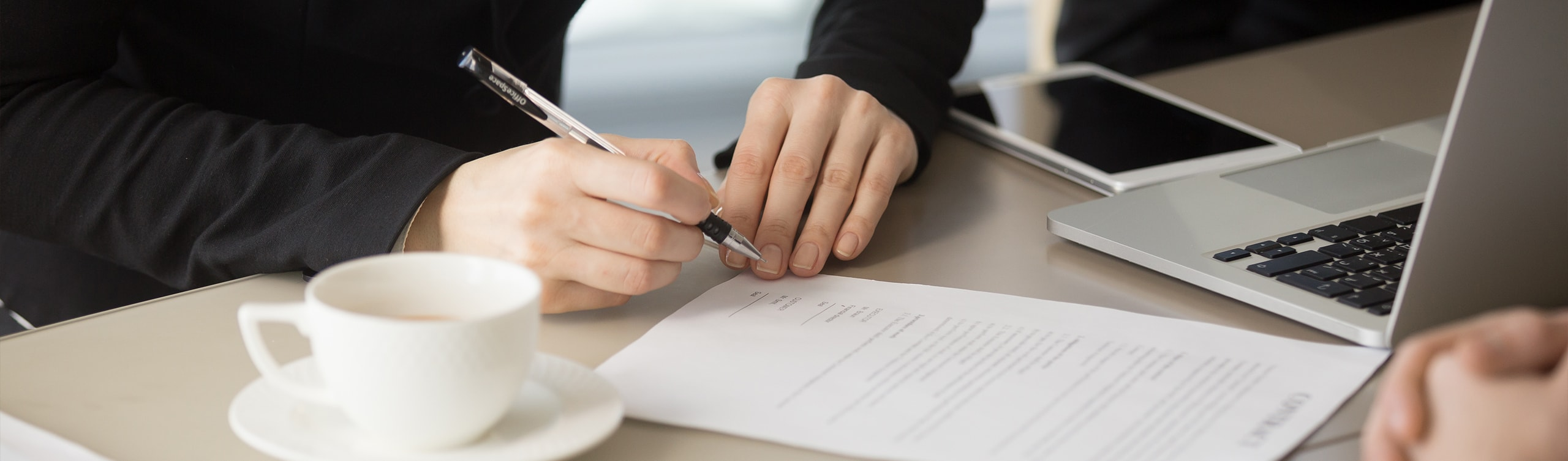 close up of woman signing a document to designate beneficiary