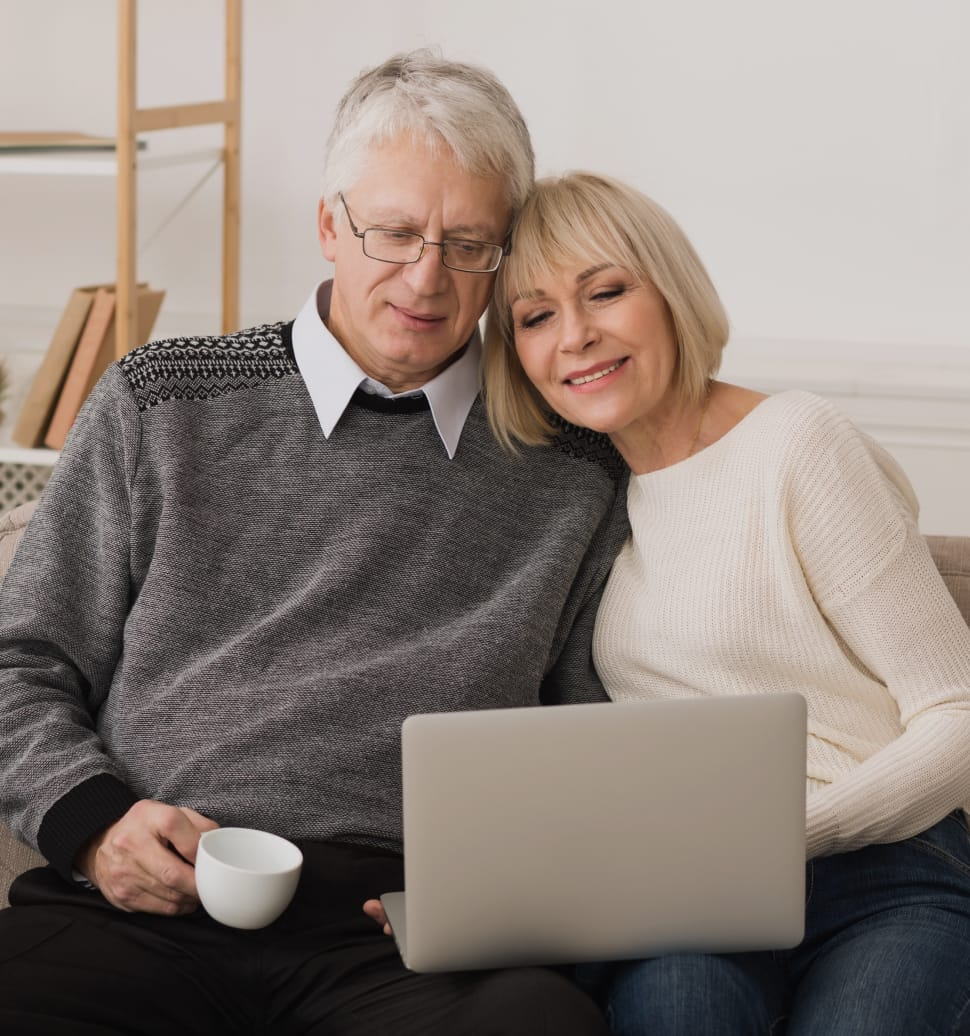 elderly couple smiling and looking at information on computer