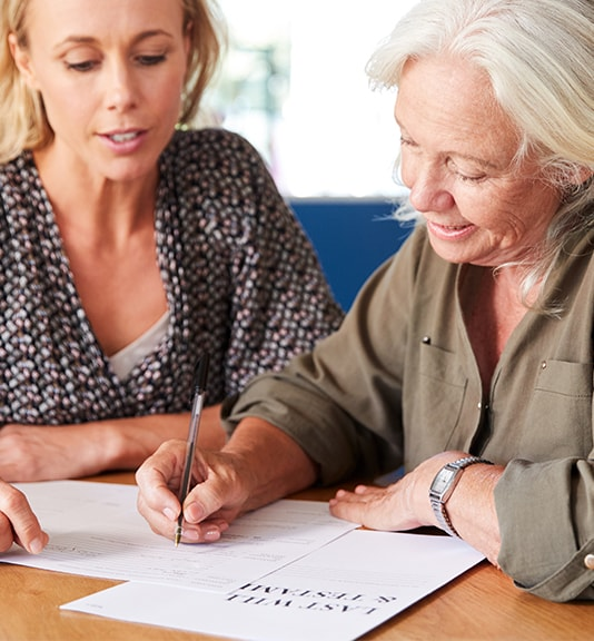 elderly woman signing form with woman