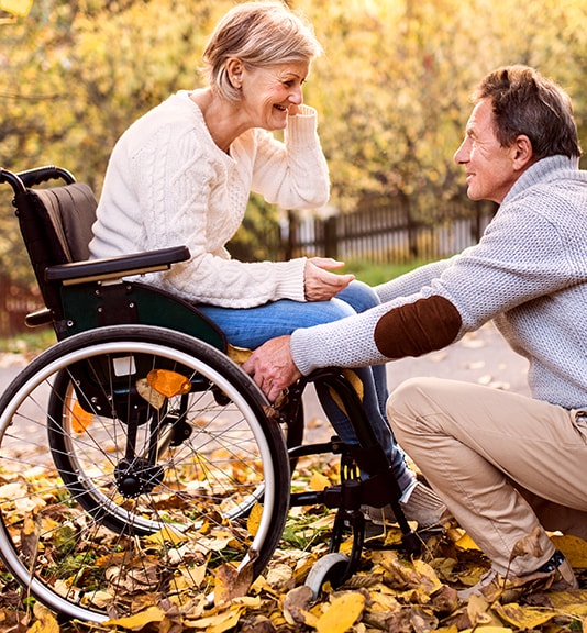 elderly man kneeling and talking to his wife in wheelchair