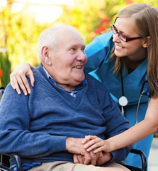 close-up of home healthcare nurse hugging elderly man
