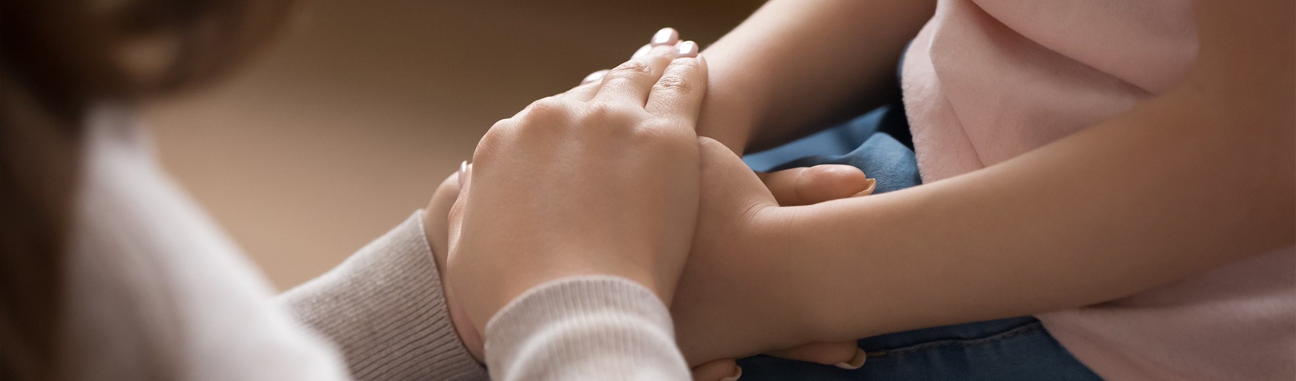 legal guardian comforts child by holding hands