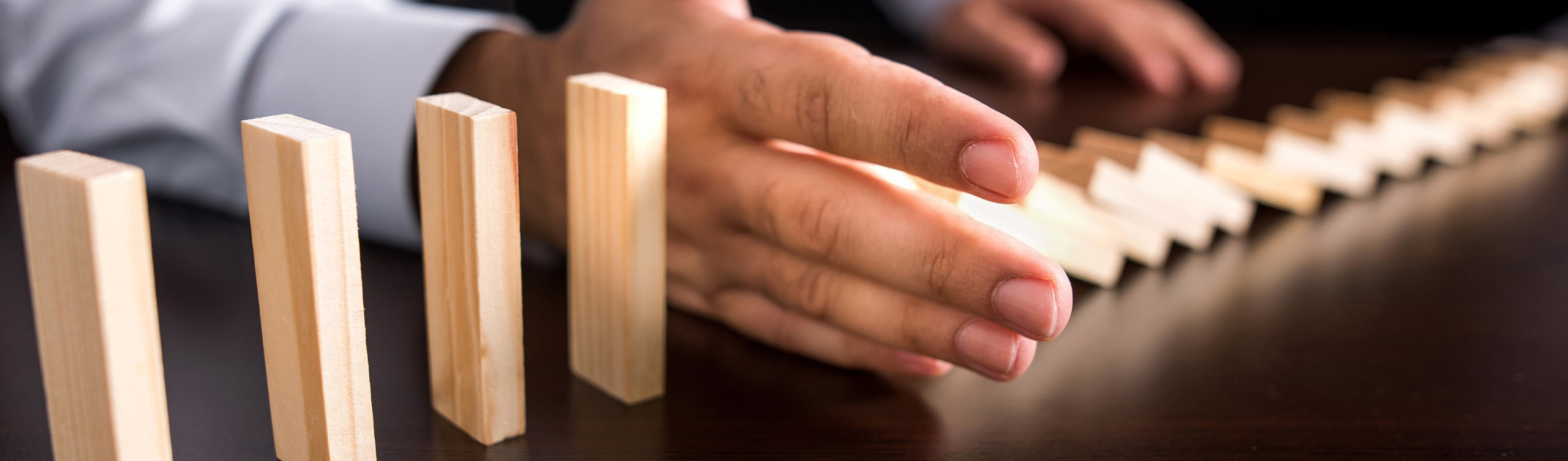 man holds out hand to stop blocks from falling, concept of asset protection